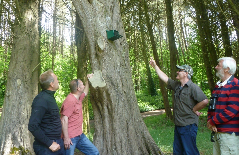 Wildlife expert Dr Nick Fox ( far right) is pictured inspecting one of the 22 feeding stations put up on the island for the red squirrels.